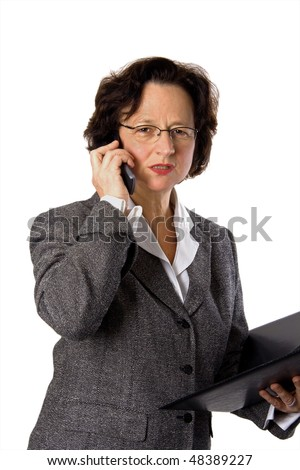 Businesswoman in a grey suit looking angry while calling on a cell phone