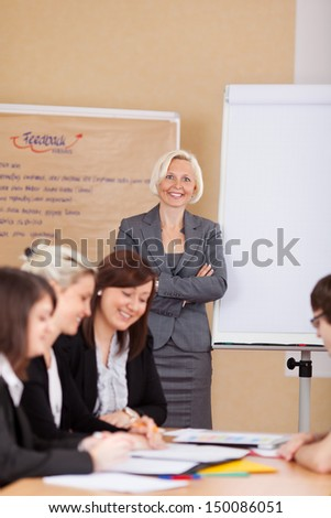 businesswoman in a meeting standing with folded arms - stock photo