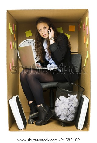 Businesswoman in a very small Cardboard Office isolated on white background