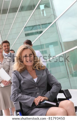 Businesswoman in a wheelchair with colleagues outside an office building - stock photo
