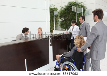 Businesswoman in a wheelchair with her colleagues at reception - stock photo