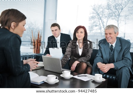 Businesswoman in an interview with three business people getting positive feedback - stock photo