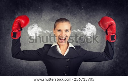 Businesswoman in boxing gloves posing with her arms up, looking at camera, shouting, smoke from her ears. Raw concrete wall as backdrop - stock photo
