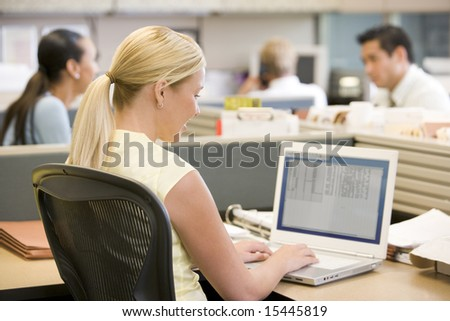 Businesswoman in cubicle using laptop - stock photo