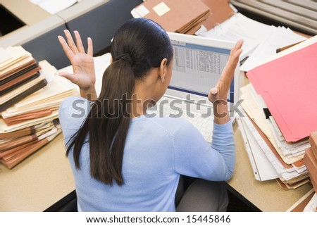 Businesswoman in cubicle with laptop and stacks of files - stock photo