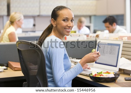 Businesswoman in cubicle with laptop eating salad - stock photo