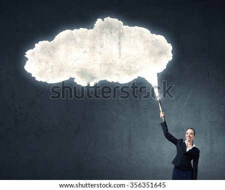 Businesswoman in darkness with flashlight in hand and blank cloud
