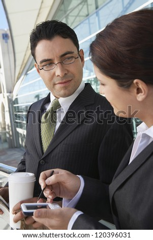 Businesswoman in discussion with businessman using PDA outside office - stock photo