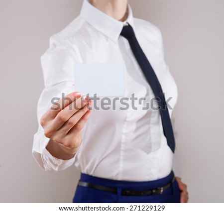 Businesswoman in formalwear showing business card, neutral background - stock photo