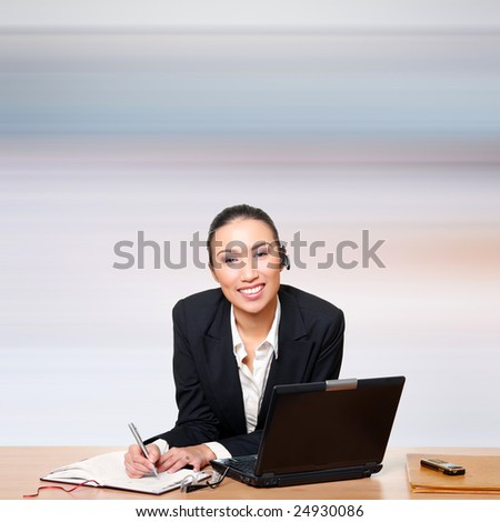 Businesswoman in front of the computer writes in a notebook. Please see some of my other business images: - stock photo