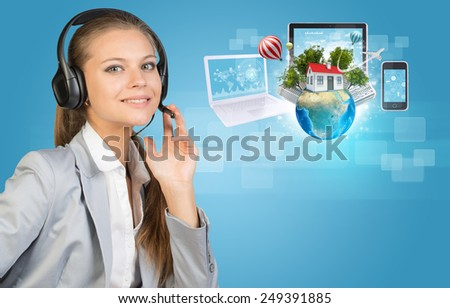 Businesswoman in headset, her hand on microphone, looking at camera, smiling. Beside are Globe with small house, high-rise buildings, trees, airplane and balloons, surrounded by computers and - stock photo