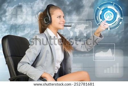 Businesswoman in headset sitting on chair using virtual interface. World map, graphs and figures over cloudy sky as backdrop