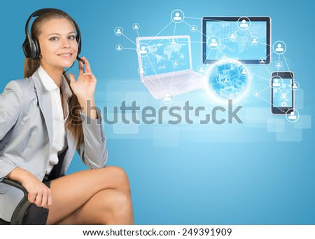 Businesswoman in headset, sitting on office chair, her hand on microphone, looking at camera, smiling. Globe, Network with people icons, laptop, tablet PC and smartphone beside, on light blue