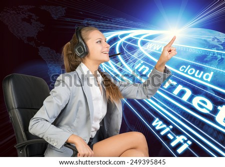 Businesswoman in headset sitting on office chair, touching spot of light with rays around, smiling. Beside is Globe surrounded by light streams of communication. World map composed of digits as - stock photo