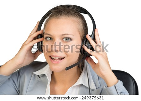 Businesswoman in headset with her hands on headset speakers, looking at camera, her lips parted. Isolated over white background
