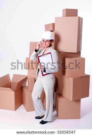 businesswoman in helmet correcting glasses and keeping clipboard, on cardboard boxes background