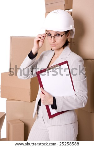 businesswoman in helmet correcting glasses keeping clipboard, on cardboard boxes background