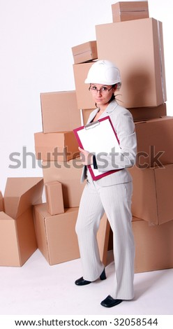 businesswoman in helmet keeping clipboard, on cardboard boxes background - stock photo