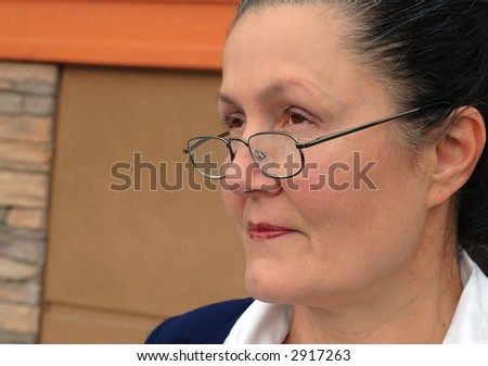Businesswoman in her late fifties in glasses and a suit - stock photo