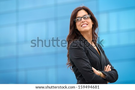 Businesswoman in leadership confident pose outside corporate building. Business woman crossing arms and smiling. - stock photo