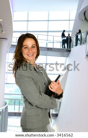 Businesswoman in modern corporate interior with management team in background. - stock photo