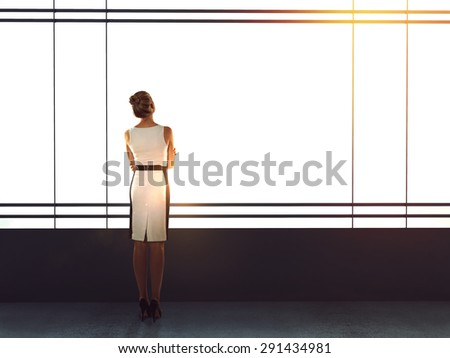 businesswoman in modern office looking to sky - stock photo