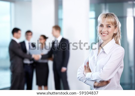 Businesswoman in office on the background of serving staff - stock photo