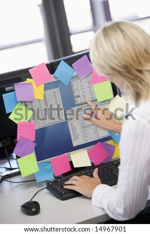 Businesswoman in office pointing at monitor with notes on it - stock photo