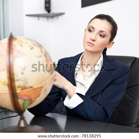 businesswoman in office space with desk globe - stock photo