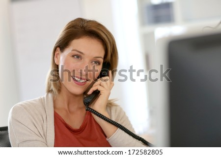 Businesswoman in office talking on the phone - stock photo