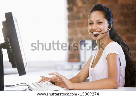 Businesswoman in office wearing headset and typing on computer smiling - stock photo