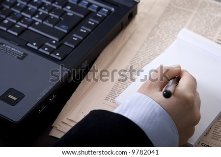 businesswoman in office with computer newspaper and notebook - stock photo