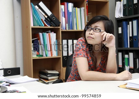 Businesswoman in office with folder background - stock photo