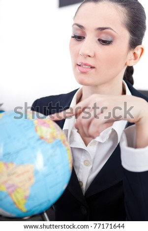 businesswoman in office with globe searching destination for new job - stock photo