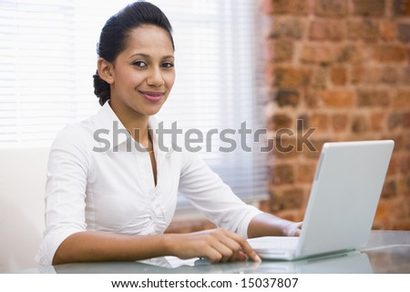 Businesswoman in office with laptop smiling - stock photo