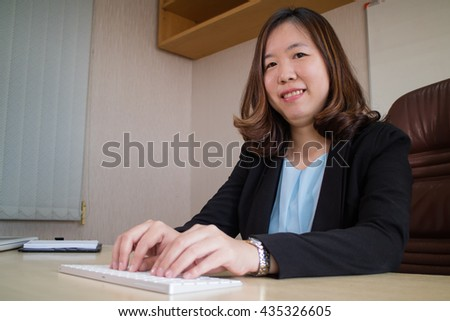 Businesswoman in office working with kebord and smiling - stock photo