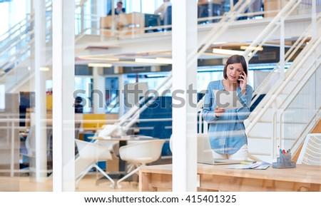 Businesswoman in open-plan office talking on phone - stock photo