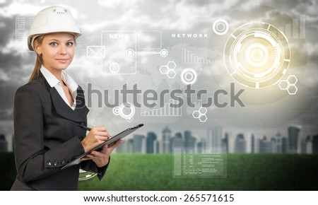 Businesswoman in suit and helmet holding clipboard, looking at camera. Blured city, grass and evening sky with flying virtual elements as backdrop - stock photo