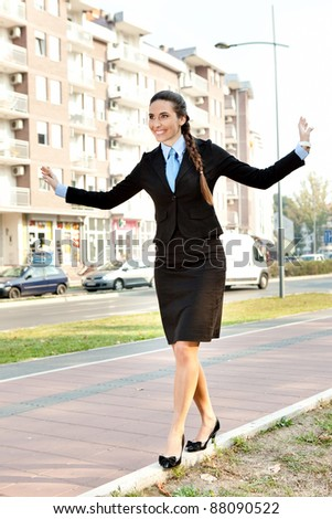 businesswoman in suit  balancing on  the curb - stock photo