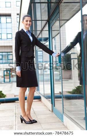 businesswoman in suit enters in her  office business , image is taken outdoors on a street - stock photo