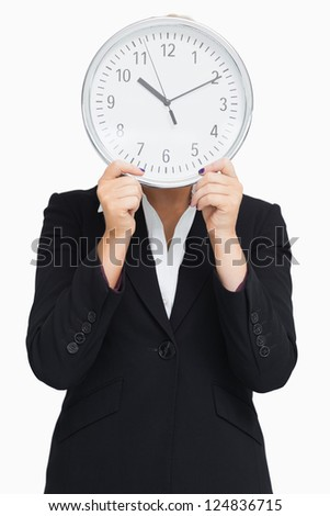 Businesswoman in suit holding a clock against white background