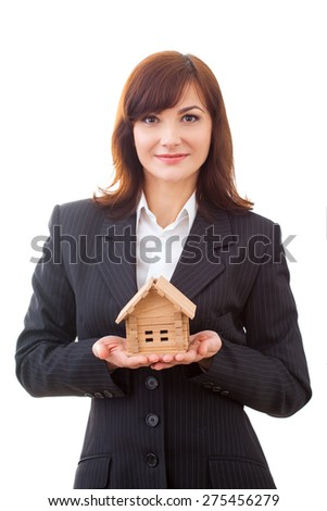 businesswoman in suit holding a small house in hand - stock photo