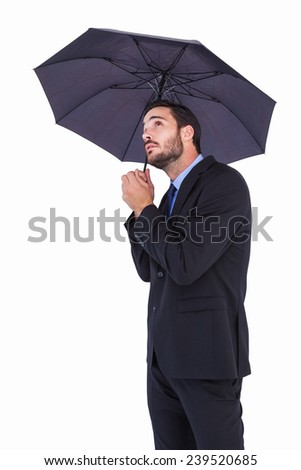Businesswoman in suit holding umbrella while looking up on white background - stock photo