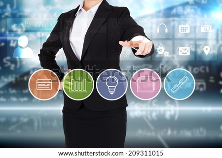 Businesswoman in suit pointing finger to business app buttons on blue background - stock photo