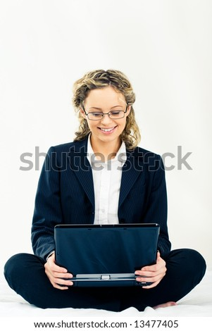 Businesswoman in suit sitting with laptop and looking at its screen over white background - stock photo