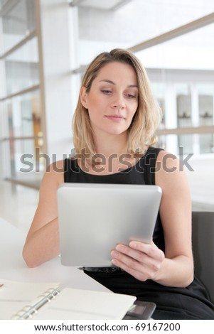 Businesswoman in the office working on electronic tab - stock photo