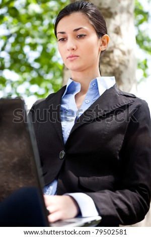 businesswoman in the park working on laptop - stock photo