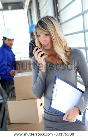 Businesswoman in warehouse using walkie-talkie - stock photo