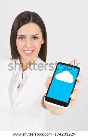 Businesswoman in white smiling showing smart phone screen with cloud computing icon. Woman using cloud on smart phone or tablet. Modern technology concept. - stock photo