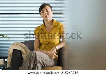 in yellow blouse sitting in office chair smiling portrait - Office Chair For Short Person